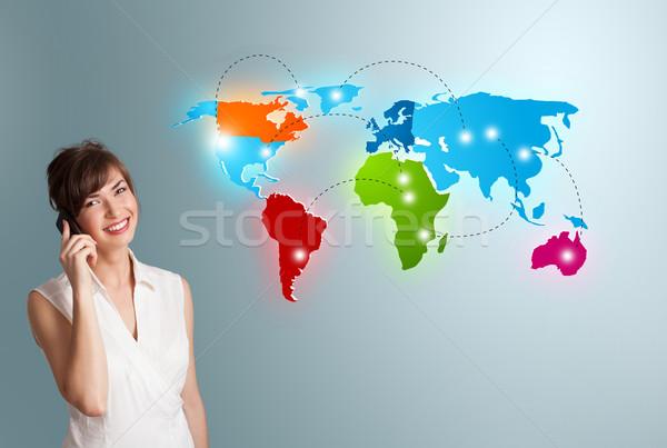 Fiatal nő készít telefonbeszélgetés színes világtérkép gyönyörű Stock fotó © ra2studio