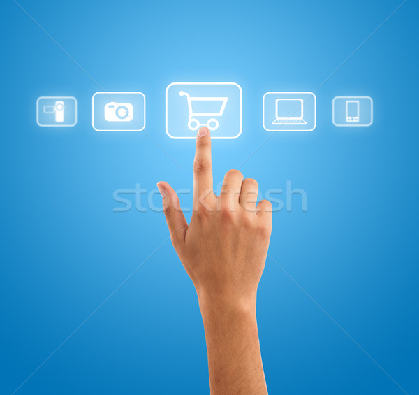 hand choosing shopping cart symbol from media icons on blue Stock photo © ra2studio