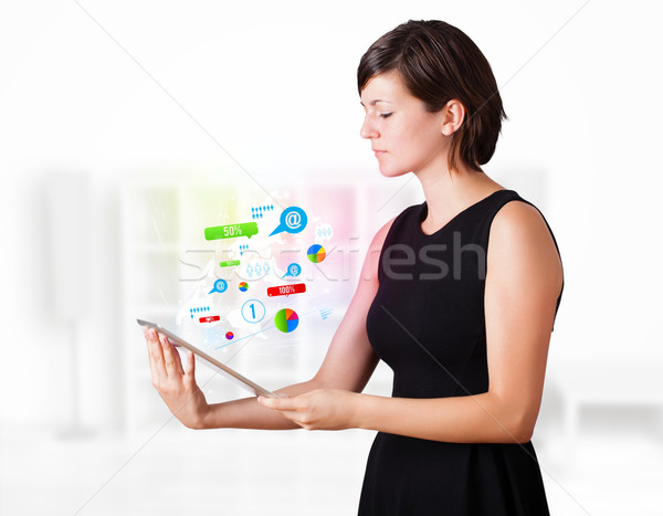 Young business woman looking at modern tablet with colourful technology icons Stock photo © ra2studio