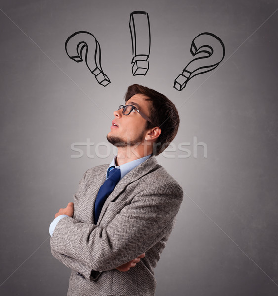 Young man thinking with question marks overhead Stock photo © ra2studio
