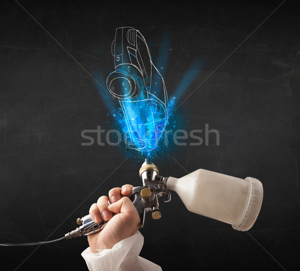 Worker with airbrush gun painting hand drawn car lines Stock photo © ra2studio