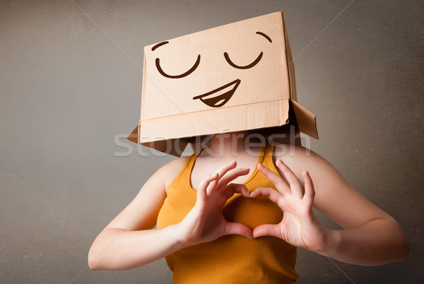 Young woman gesturing with a cardboard box on her head with smil Stock photo © ra2studio