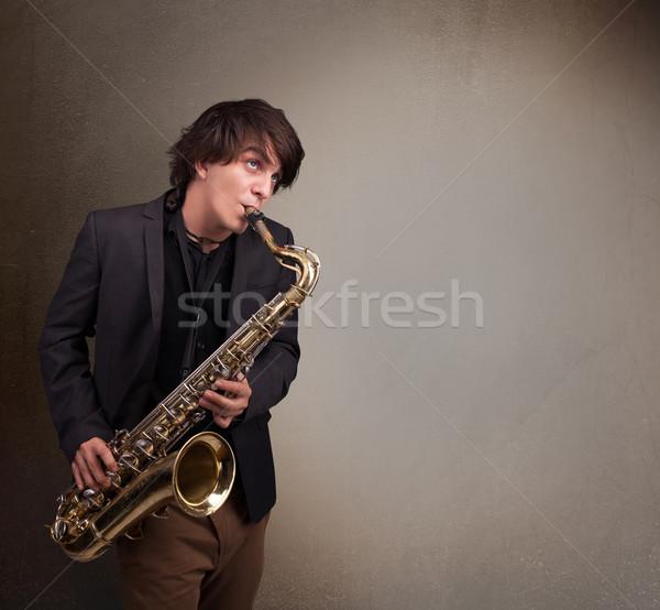 Young musician playing on saxophone Stock photo © ra2studio