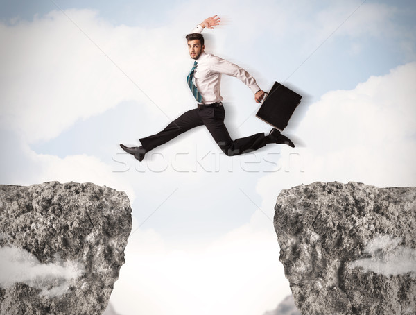 Stock photo: Funny business man jumping over rocks with gap