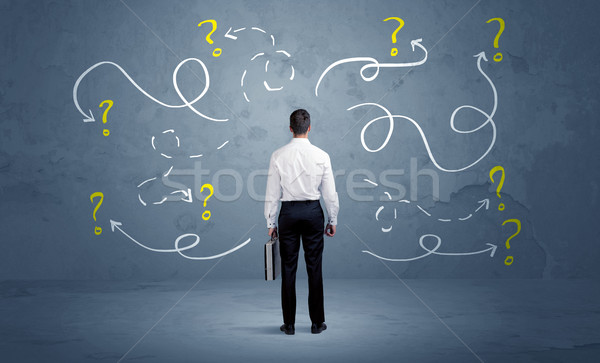 Unsure businessman with question marks Stock photo © ra2studio