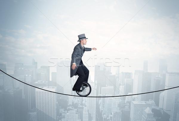 Trotzen guy Reiten Seil über Stadtbild Stock foto © ra2studio