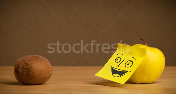 Apple with post-it note smiling at kiwi Stock photo © ra2studio