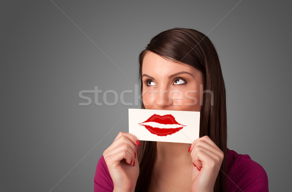 Happy pretty woman holding card with kiss lipstick mark Stock photo © ra2studio