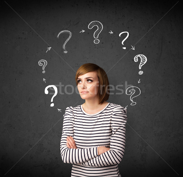 Young woman thinking with question mark circulation around her h Stock photo © ra2studio