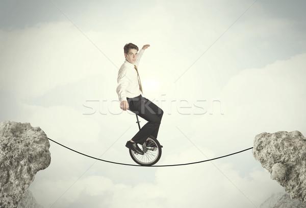 Brave business man riding an mono cycle between cliffs Stock photo © ra2studio