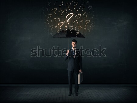 Businessman with umbrella and a lot of drawn question marks Stock photo © ra2studio