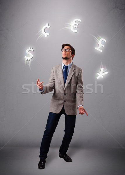 young man standing and juggling with currency icons Stock photo © ra2studio