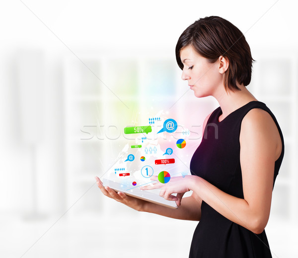 Stock photo: Young business woman looking at modern tablet with colourful technology icons