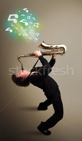 Fiatal zenész játszik szaxofon hangjegyek vonzó Stock fotó © ra2studio