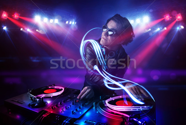 Stock photo: Disc jockey playing music with light beam effects on stage