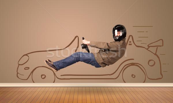 Happy man driving an hand drawn car on the wall Stock photo © ra2studio