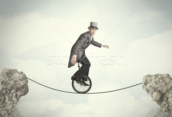 Brave business man riding an mono cycle between cliffs Stock photo © ra2studio