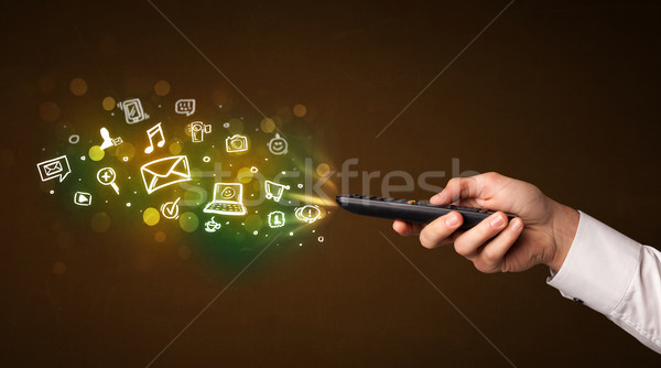 Hand with remote control and social media icons Stock photo © ra2studio