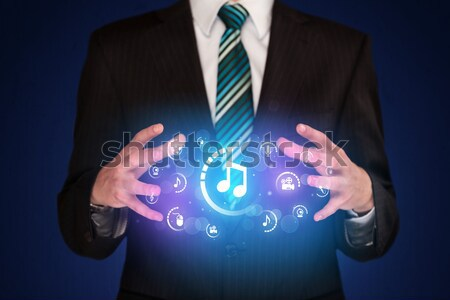 Férfi tart digitális multimédia ikonok üzletember Stock fotó © ra2studio