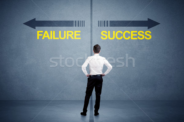 Businessman standing in front of success and failure arrow concept Stock photo © ra2studio
