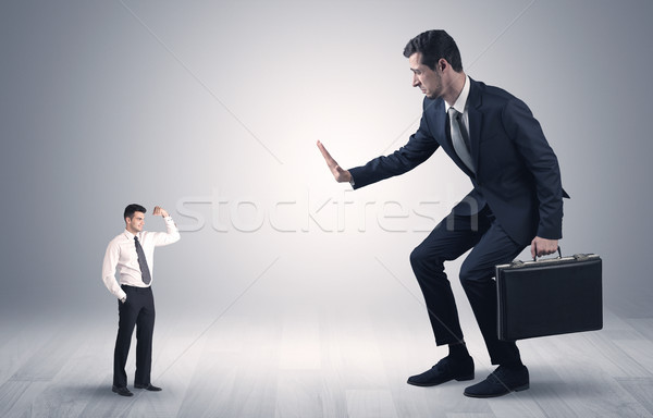 Giant businessman scared of small businessman Stock photo © ra2studio