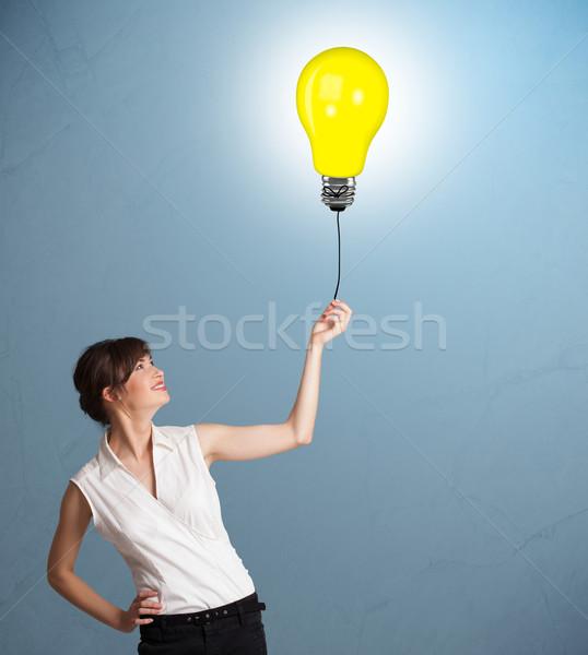 Csinos hölgy tart villanykörte léggömb fiatal nő Stock fotó © ra2studio