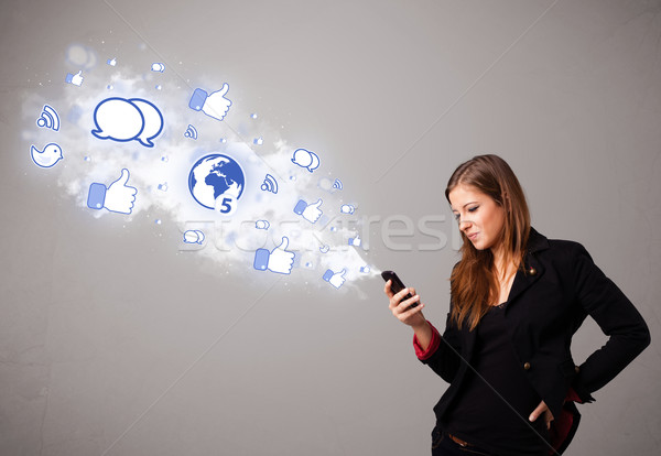 Pretty young girl holding a phone with social media icons Stock photo © ra2studio