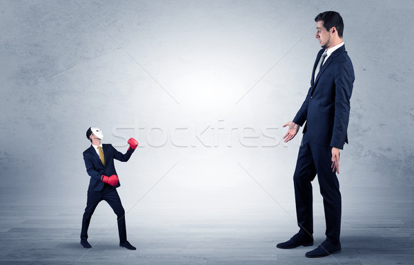 Businessman begging for small masked businessman Stock photo © ra2studio