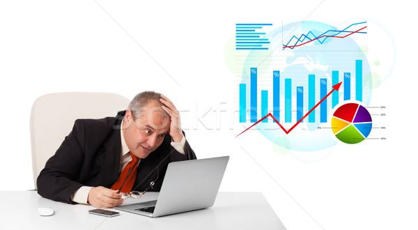 Businessman sitting at desk with laptop and statistics Stock photo © ra2studio