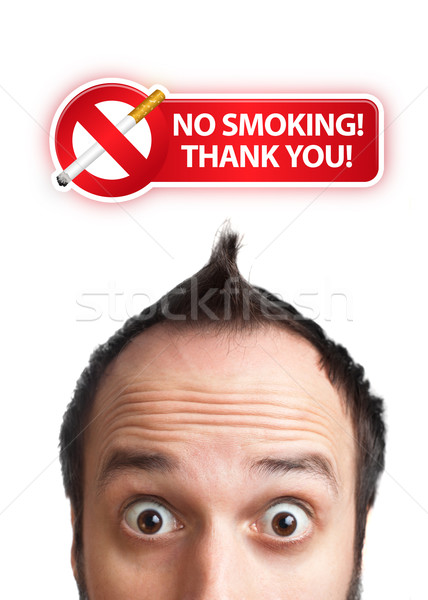 Young man with NO SMOKING sign over his head Stock photo © ra2studio