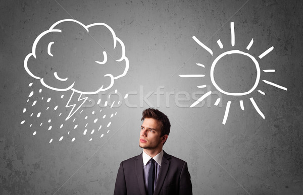 Businessman standing between a sun and a rain drawing Stock photo © ra2studio