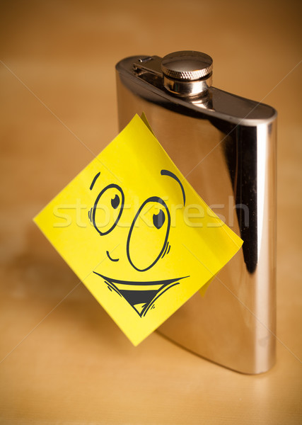 Post-it note with smiley face sticked on hip flask Stock photo © ra2studio