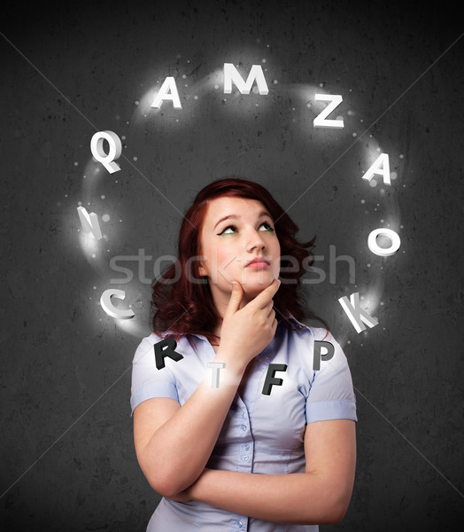 Stock photo: Young woman thinking with letter circulation around her head