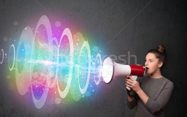 Young girl yells into a loudspeaker and colorful energy beam com Stock photo © ra2studio