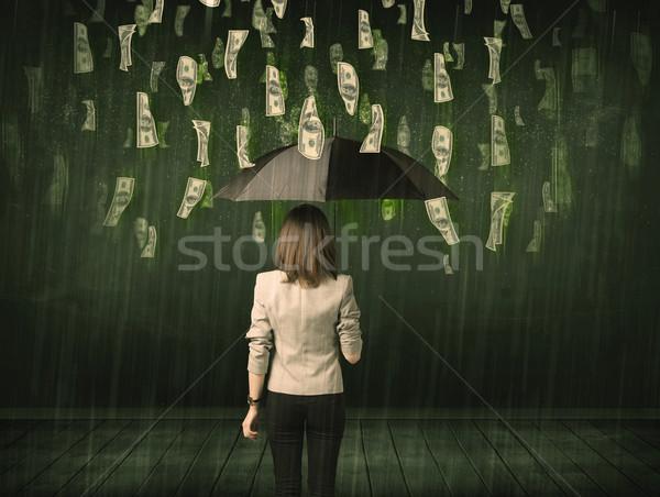 Stock photo: Businesswoman standing with umbrella in dollar bill rain concept