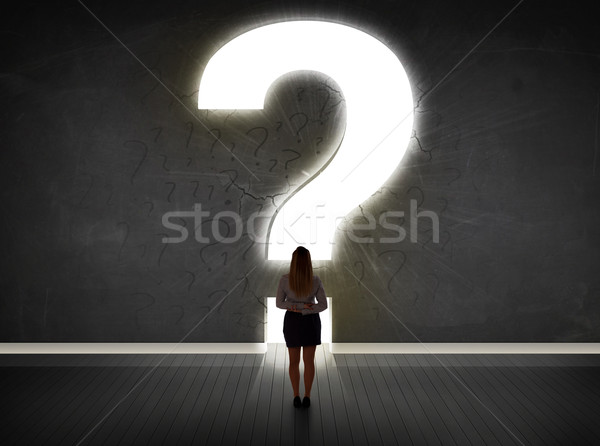 Business woman looking at wall with a bright question mark  Stock photo © ra2studio