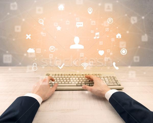 Elegant businessman hand typing social media icons around Stock photo © ra2studio