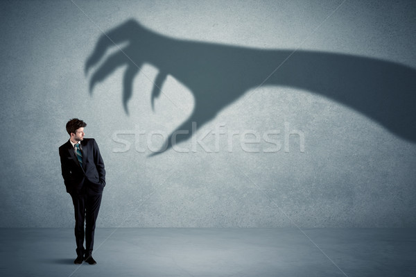 Business person afraid of a big monster claw shadow concept Stock photo © ra2studio