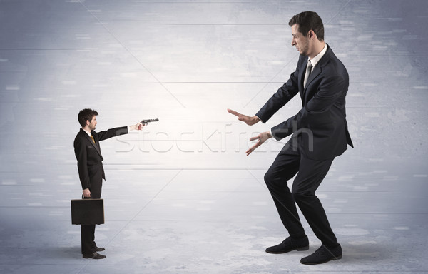 Small businessman shooting giant businessman Stock photo © ra2studio