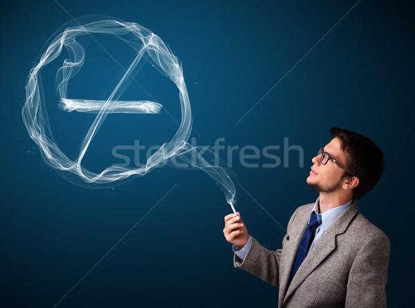 Young man smoking unhealthy cigarette with no smoking sign Stock photo © ra2studio