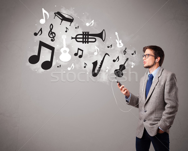 attractive young man singing and listening to music with musical notes and instruments Stock photo © ra2studio