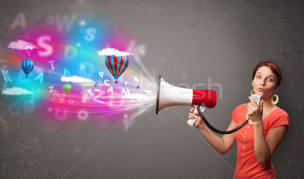Stock photo: Cute girl shouting into megaphone and abstract text and balloons come out