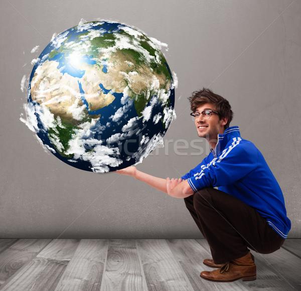 Stock photo: Good-looking man holding 3d planet earth