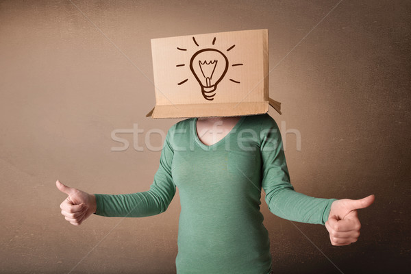 Young woman gesturing with a cardboard box on her head with ligh Stock photo © ra2studio
