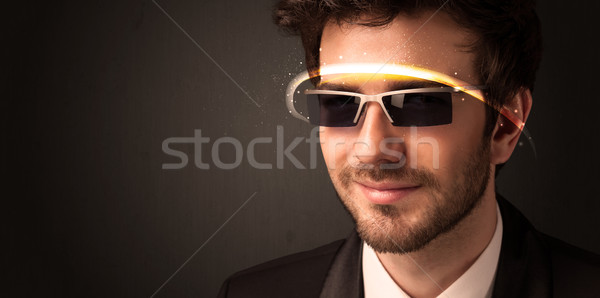 Stock photo: Handsome man looking with futuristic high tech glasses