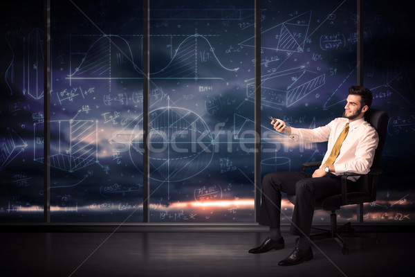 Businessman Holding Tablet In Office Room With Graph Charts