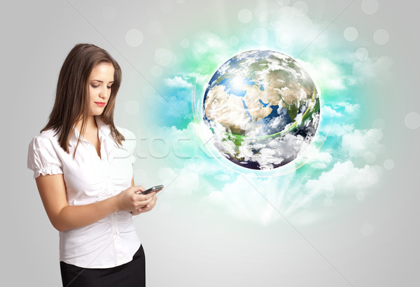 Young woman with earth and cloud concept Stock photo © ra2studio