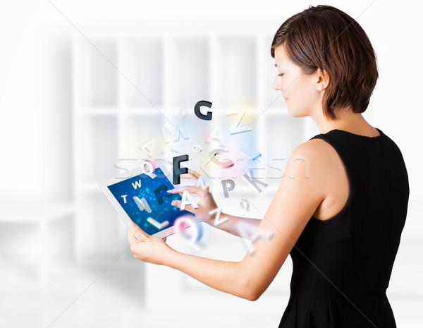 ストックフォト: 若い女性 · 見える · 現代 · タブレット · アルファベット · 小さな