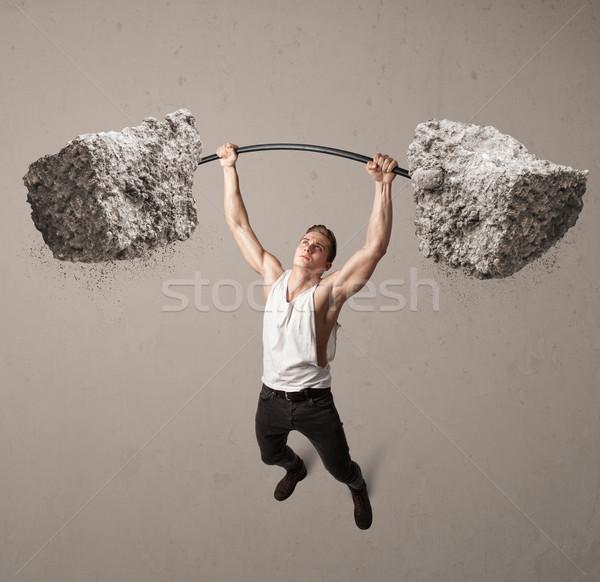 muscular man lifting large rock stone weights Stock photo © ra2studio