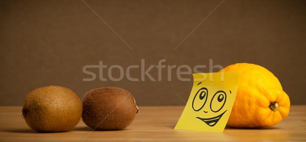 Lemon with post-it note looking at kiwis Stock photo © ra2studio